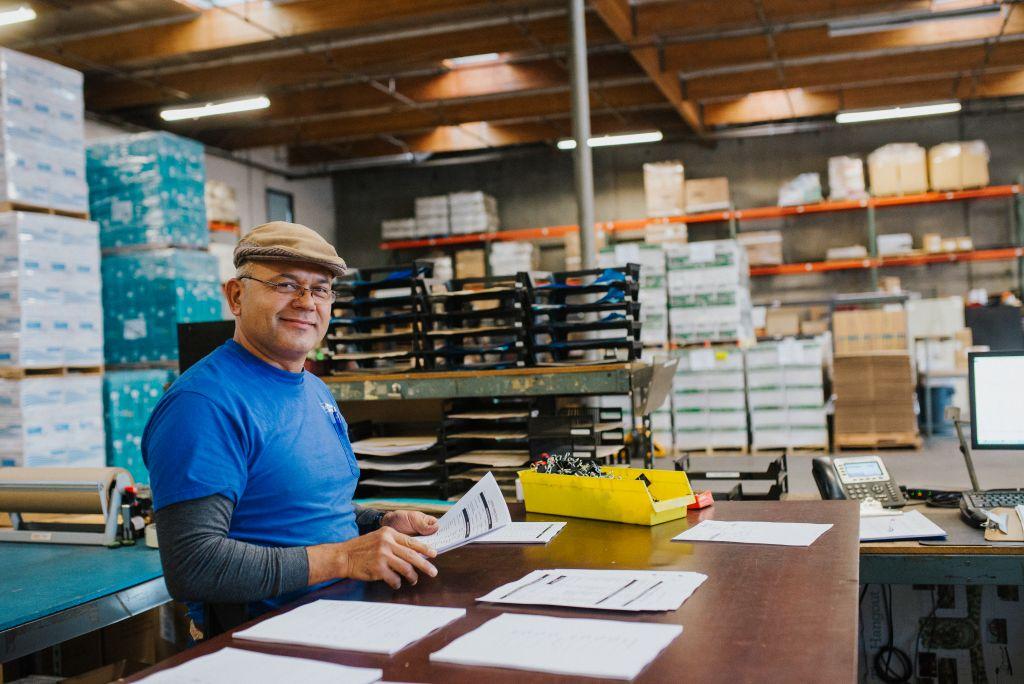 Our team member organizes invoices and paperwork in the warehouse.