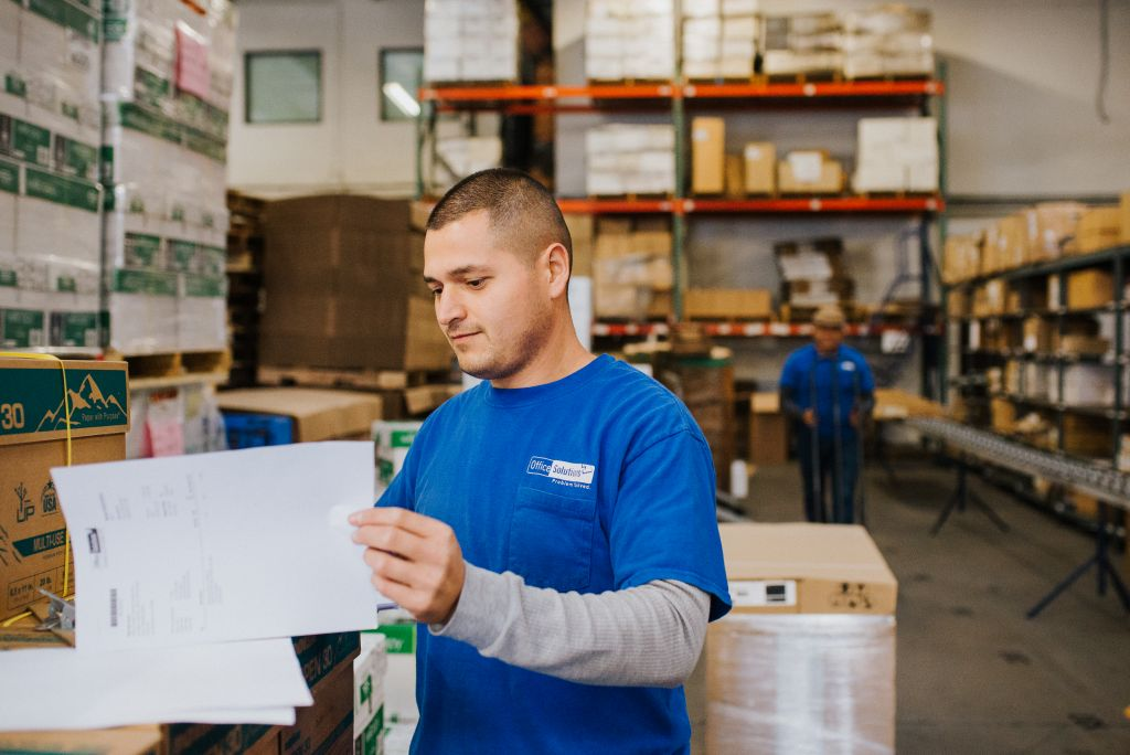 Our employee prepares paperwork in the warehouse.